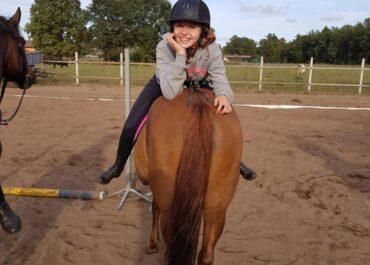 dziewczynka siedząca tyłem na koniu